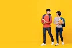 Asian girl and boy students with bags holding books in a conversation while walking towards class college isolated against yellow studio background