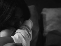 Asian girl are sitting on the sofa in house and looked sad. Black and white images of Thai women are suffering from depression.