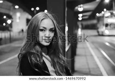 Asian Girl at Hong Kong's Ding Ding Tram waiting stop in black and white photography with hair blowing in the wind. #1469670992