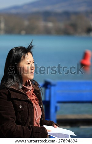 asian girl beside the lake, reading a book