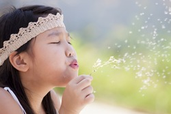 Asian girl blowing dandelion