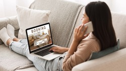 Asian girl booking hotel online, talking on phone with reservation team, sitting on couch at home at using laptop