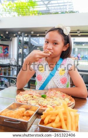 Asian girl child eat pizza in a restaurant