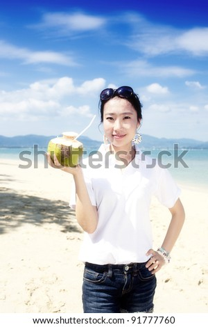 Asian girl drinking coconut on the beach,Phuket,Thailand