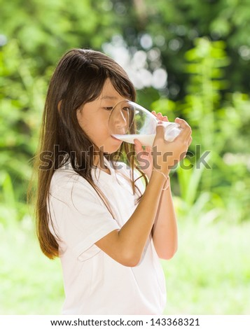 Asian girl drinking milk in the park