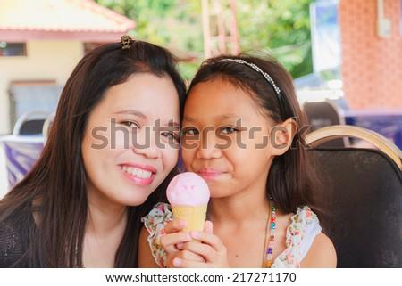 Asian girl eat Ice Cream Cone in restaurant.