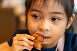 Asian girl Eating Chicken. child eating a chicken nuggets