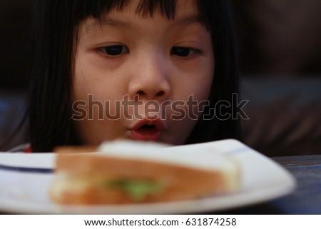 Asian girl eating sandwich  #631874258