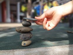 Asian girl hand putting flat stone piece on top of a balance stack of stones, risking tumbling down of them all