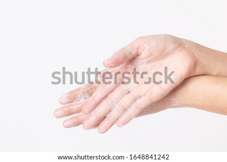 Asian girl hands are washing with soap bubbles on white background