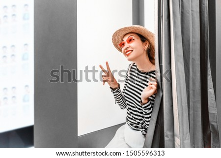 Asian girl having fun and making faces in the photo booth. The concept of small business in the field of photo printing
