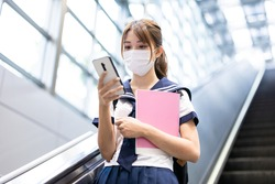 Asian girl high school student take escalator in the mrt station with facial mask and use mobile phone