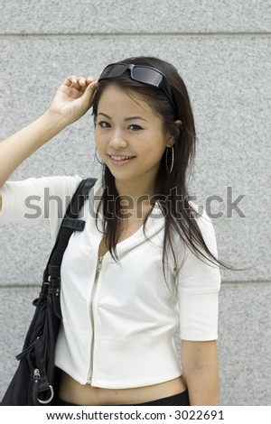 Asian girl holding pair of sunglasses