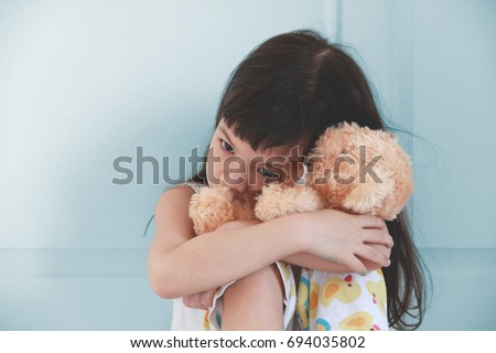 Asian girl hug her doll and cry or scare or sad or feel bad.Sitting on the bed.Selective focus