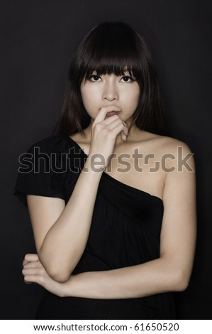 Asian girl in black clubbing dress thinking