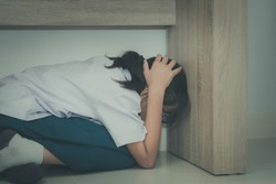 Asian girl in school uniform sitting under the table with panicky when the earthquake with concept