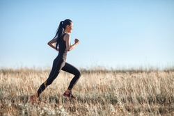 Asian girl in sportswear running across field, morning workout. Eastern girl doing sports. Side view of active athletic young woman running on blue sky background. Photo with copy space