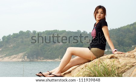 asian girl in the coastal with the sea and mountain background with innocent face and pose side view on Lamma Island in hong kong