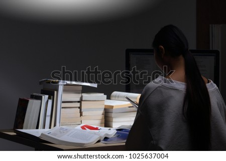 Asian Girl in white shirt reading many textbooks on table with many high stacking of international Books Journal Report, Woman works hard during night time, feel asleep tired, low exposure turn back #1025637004