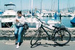asian girl is using her mobile phone while taking a break from bike ride at a harbor with boats in Sausalito city, California during summer holiday.