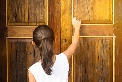 Asian girl knocking the vintage wooden door