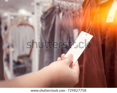 Asian girl looking at the price tag in the store #729827758