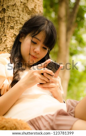 asian girl playing cell phone with happy face