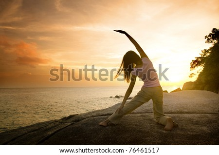 asian girl posing yoga on beautiful beach during sunset - stock photo