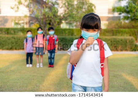 Asian girl preschool child student wearing healthy face mask sneeze with friends in background. WHO recommends at least 6 feets of distance between yourself and people who are coughing or sneezing.