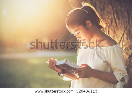 asian girl reading book at park ...