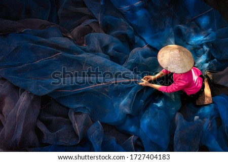 Asian girl sew the fishnet. Fisherman woman Repairs Fishing Net. Needle with thread in fisherman hand repairing net in home.