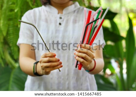 Asian girl show many plastic straws and one stainless straw in her hands with green garden background.Use steel tube for Replacement plastic,can save the earth.Reduce global warming concept. Foto stock ©