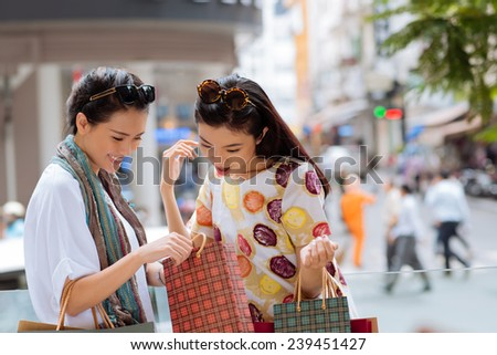 Asian girl showing something in the shopping bag to her friend