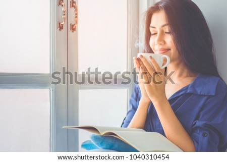 Asian girl sitting by the window. She is smiling and holding a cup of coffee in hand split up in order to inhale the aroma of coffee. Amidst the mild morning sun shines through the glass window.