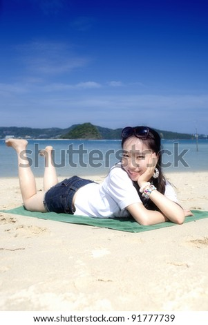 Asian girl sitting on the phuket beach,Thailand - stock photo