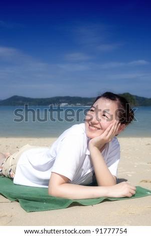 Asian girl sitting on the phuket beach,Thailand