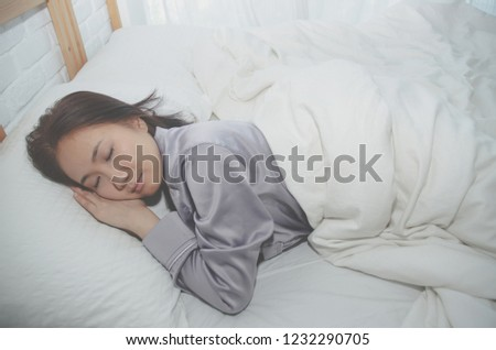 59f11b19d6 Asian girl sleeps in gray pajamas and shorts.On the bed in the white bedroom