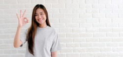 Asian girl smiling face showing approval, Happy young asia woman showing ok hand sign while standing over white brick wall background with copy space,  Positive people gesture