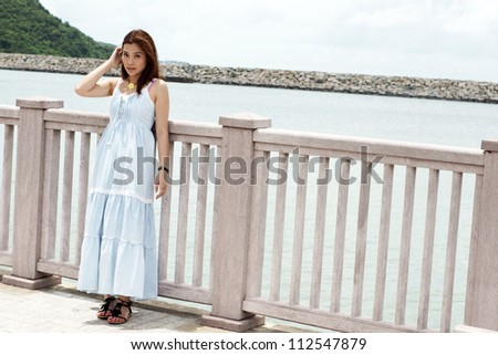 asian girl stand alone and waiting someone lying on the fences with the background of natural sea level and pier in asian oriental town
