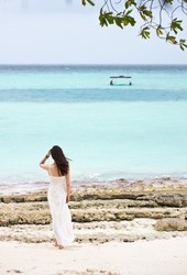asian girl standing on the beach watching towards sea