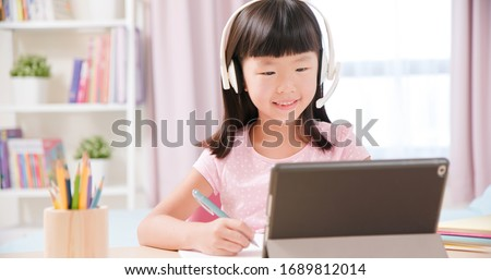 Asian girl student wear headset microphone and use tablet pc to have online language class happily at home