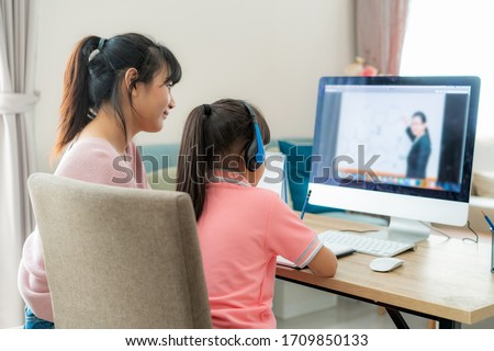 Asian girl student with mother video conference e-learning with teacher on computer in living room at home. Homeschooling and distance learning ,online ,education and internet.