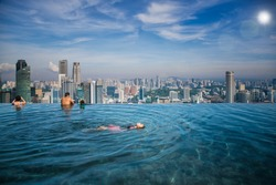 Asian girl swim in swimming pool on the roof top of hotel in Singapore city, Singapore and summer concept