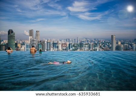 Asian girl swim in swimming pool on the roof top of hotel in Singapore city, Singapore and summer concept #635933681