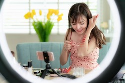 Asian girl teat lip color on her arm in her clip with donus light, this image can use for vlog, vlogger, clip, sales, online and review of cosmetic concept