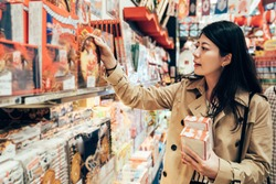 asian girl traveler in her business trip visiting local specialty shop in dotonbori osaka japan choosing souvenir for family. young lady looking holding the japanese cookie in the store.