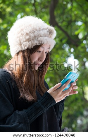Asian girl using cell phone outdoor