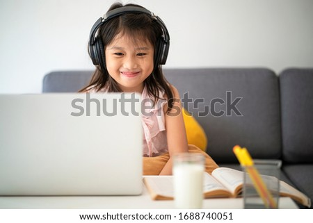 Asian girl using Laptop computer for online study homeschooling during home quarantine. homeschooling, online study, home quarantine, online learning, corona virus or education technology concept