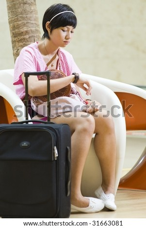 asian girl waiting at the airport terminal impatiently