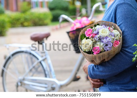 Asian girl waiting for boyfriend prepares a bouquet for him. Hold it in the embrace, That is love. May your Valentine's Day be filled. You are so special. Background blurred with bicycles.